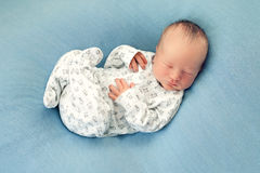 Newborn boy asleep on a blue background in white pajamas with a Royalty Free Stock Photography