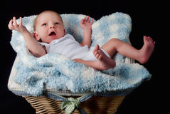 Newborn boy in a basket. Caucasian newborn baby boy in a basket on a black background Stock Photo