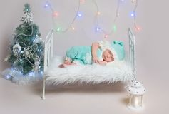 Newborn boy sleeping on small cot. Newborn boy in blue costume sleeping on small cot with Christmas decoration around it. Colourful girlands on the background Royalty Free Stock Photography