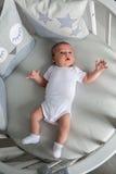 Newborn boy lies in a round bed Stock Photo