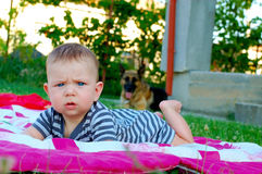 Newborn boy lying on the pink and white blankets on the green grass outside and looking at the camera stock photo