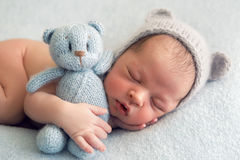 Newborn boy in a naked hat lies on a light blanket. With a blue knitted bear Stock Photo