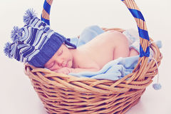 Newborn boy sleeping in basket Stock Photo