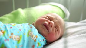 Newborn boy sleeping in her bed in the maternity hospital. cry stock footage