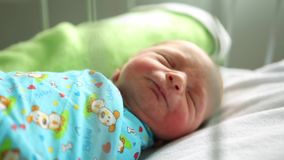 Newborn boy sleeping in her bed in the maternity hospital. He wants to eat stock video