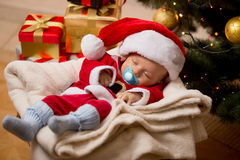 Newborn boy sleeping in living room at Christmas tree and boxes Stock Photography