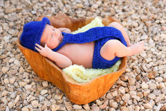 Newborn boy wearing blue fedora, tie, diaper cover. A cute newborn baby boy lies in a wooden bowl wearing a knitted royal blue fedora, tie, and diaper cover royalty free stock photo