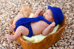 Newborn boy wearing blue fedora, tie, diaper cover. A cute newborn baby boy lies in a wooden bowl wearing a crocheted royal blue fedora, tie, and diaper cover Royalty Free Stock Photography