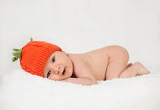 Newborn boy wearing pumpkin hat Stock Photography