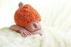 Newborn in a cap pumpkin. Sweet sleeping baby with pumpkin hat stock photos