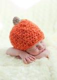 Newborn in a cap pumpkin. Sweet sleeping baby with pumpkin hat stock photo
