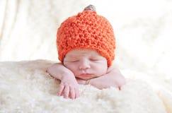 Newborn in a cap pumpkin. Sweet sleeping baby with pumpkin hat royalty free stock photo