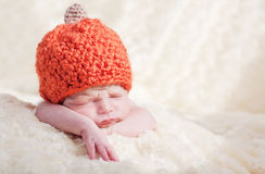 Newborn in a cap. Sweet sleeping baby with pumpkin hat royalty free stock image
