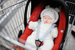 Newborn in car seat in a shopping cart Stock Photos