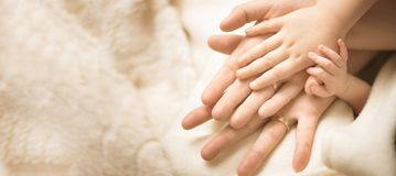 Newborn child hand. Closeup of baby hand into parents hands. Family, maternity and birth concept. Banner