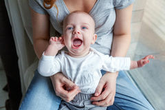 Newborn child laughs in the arms of his mother Royalty Free Stock Photo