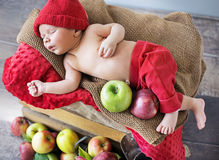 Newborn child sleeping on the box of apples Stock Images