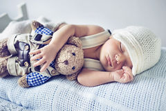 Newborn child sleeping with a teddy bear Stock Image