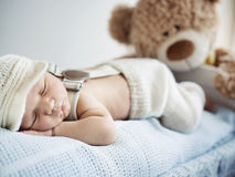 Newborn child sleeping with a toy Stock Images