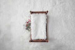 Newborn Christmas backdrop - wooden bed with white faux fur, snow covered branches with red berries on white background