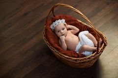 Newborn with a crown in  basket on  floor Royalty Free Stock Photo