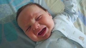 Newborn Crying Baby Boy. Slow motion shot of a closeup portrait of crying newborn baby boy stock video footage