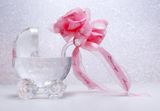 Newborn crystal stroller with ribbon bow. Crystal baby stroller with pink bow on a textured glass background Stock Photo