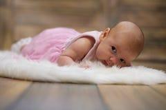 Newborn cute baby lying on white fur skin Royalty Free Stock Photo