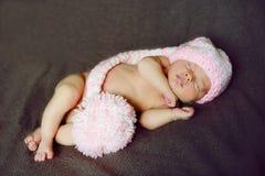 Newborn. Cute little newborn babywearing pink pompom hat Stock Photography