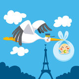 Newborn Delivery. Cute stork flying the skies over Eiffel Tower carrying a newborn baby for delivery Royalty Free Stock Photography
