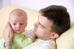 Newborn in Father's embrace. Baby kised and embraced by its father royalty free stock photo
