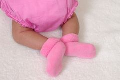 Newborn feet with pink socks Stock Photos