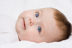 Newborn Girl. Newborn Caucasian baby girl laying on her back, with her face turned toward the camera Royalty Free Stock Photos