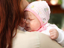 The newborn girl in a cap. The newborn girl on mum's hands Royalty Free Stock Image