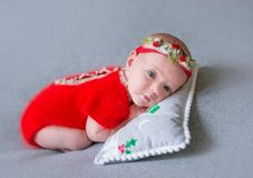 Newborn girl in a Christmas suit is sleeping on a New Year`s pillow. A newborn girl in a Christmas suit is sleeping on a New Year`s pillow Royalty Free Stock Photos