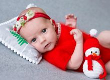 Newborn girl in a Christmas suit is sleeping on a New Year`s pillow. A newborn girl in a Christmas suit is sleeping on a New Year`s pillow Stock Photography