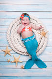 The newborn girl is crying in a mermaid suit the ropes on wooden boards. Royalty Free Stock Photo