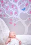 Newborn girl in cute baby room. Gentle stylish interior of bedroom, beautiful picture on wallpaper, happy childhood concept Stock Photo