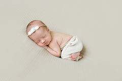 Newborn girl in hairband sleeping on her side Royalty Free Stock Photos