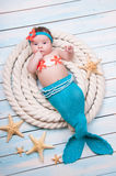 The newborn girl in a mermaid costume, lies in the ropes on wooden boards. Stock Photography