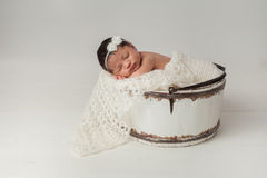 Newborn Girl Sleeping in Wooden Bucket. A three week old newborn baby girl sleeping in a little, wooden bucket. She is wearing a cream colored bow headband. Shot Royalty Free Stock Photography