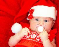Newborn girl wearing Santa hat Stock Photos