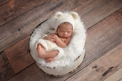 Newborn Girl Wearing a White Bear Hat. An overhead shot of an eleven day old newborn baby girl sleeping in a wooden bucket. She is wearing a crocheted, white stock image