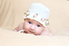 Newborn girl in white cap with flouwers royalty free stock photography