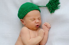 Newborn in green knitted hat stock photography