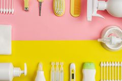 Newborn healthcare products and grooming kit, flat lay. Cotton buds, gauze, hair comb, brush, scissors on yellow and pink background with small copy space stock photos
