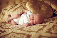 Newborn healthy baby 2 weeks old is lying in a posh bedroom on t. He parent's bed and smiles. A small child in the comfort of your room Stock Photography