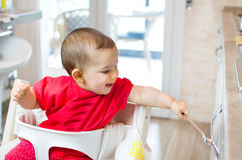 Newborn high chair play beating kitchen drawer spoon - heuristic Royalty Free Stock Image