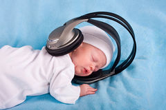 The newborn kid listening to music Stock Photography