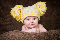 Newborn in knitted winter hat on a beige background. Royalty Free Stock Photos